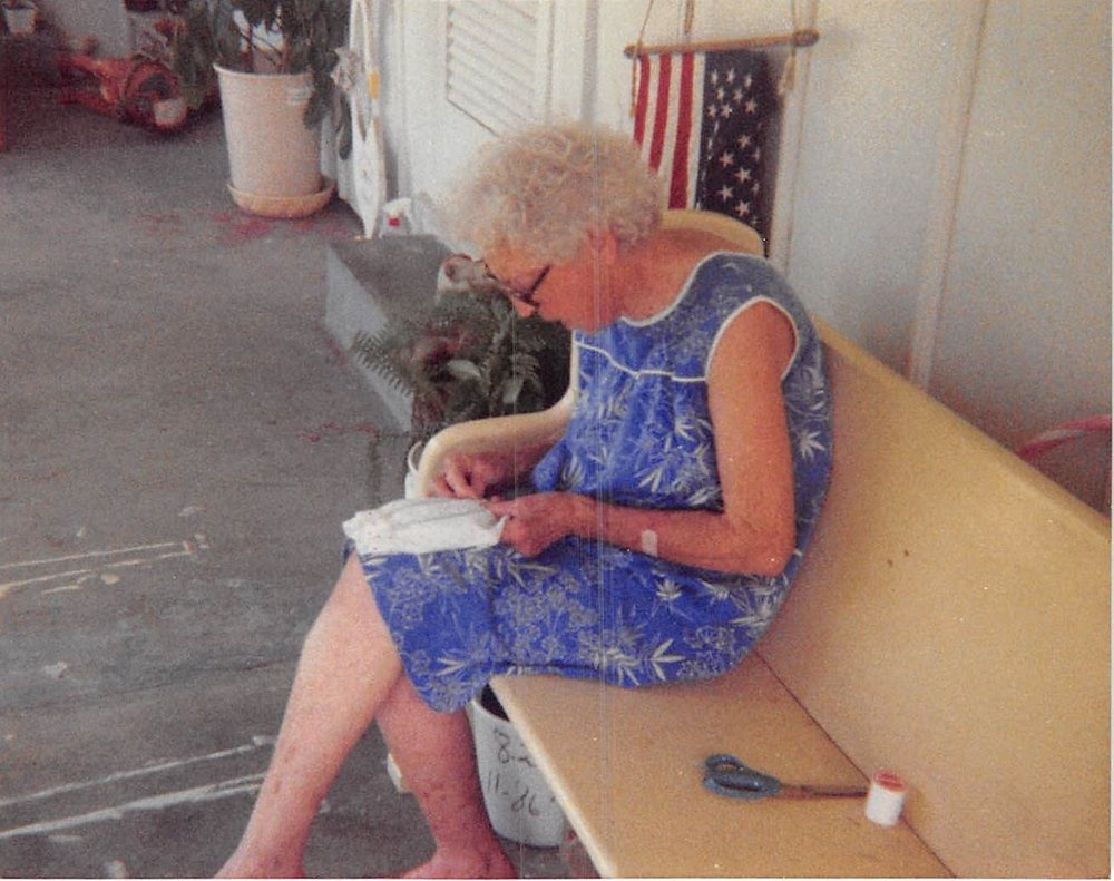 Grandma sewing on the front porch pew, and weirdly enough my porcelain dog statue in the background.