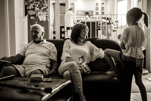 Grandparents on sofa with granddaughter.