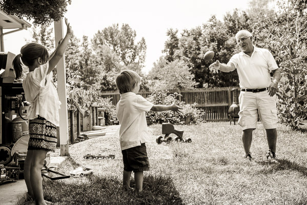 Grandpa tossing football to grandkids in back yard.