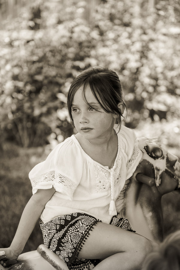 Beautiful young girl sitting backward on rocking horse.