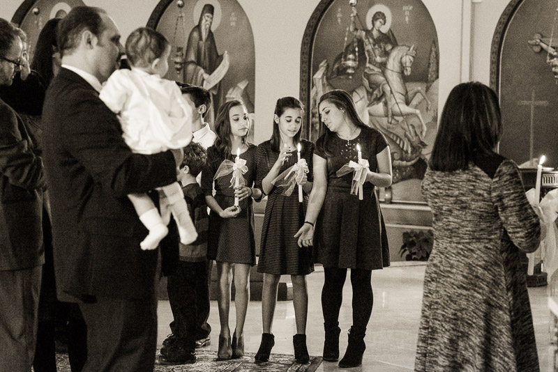 Teen girls holding their baptism candles during the ceremony.