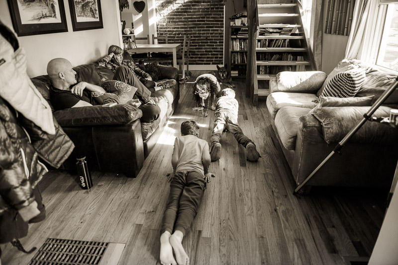 Family doing yoga together in the living room.