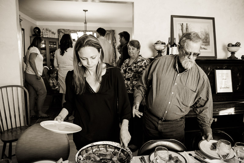Woman looks on as two people serve themselves dinner.