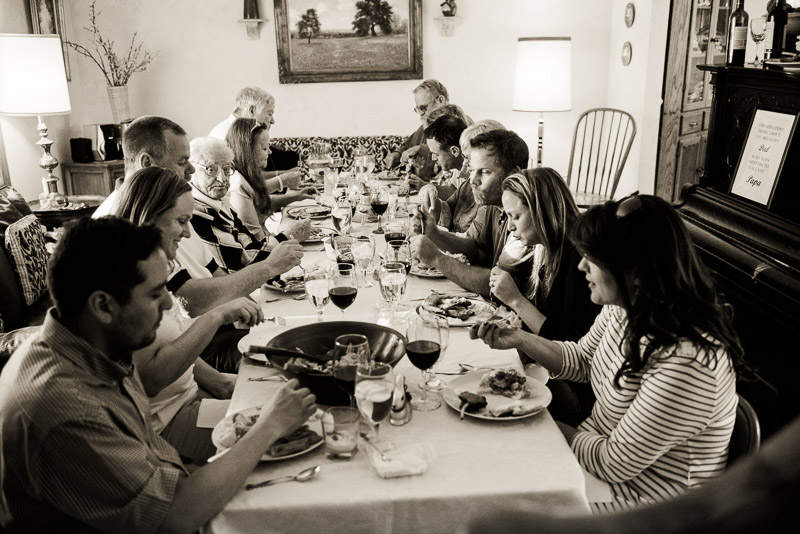 Thanksgiving documentary family photography Denver of everyone sitting at the dinner table eating.