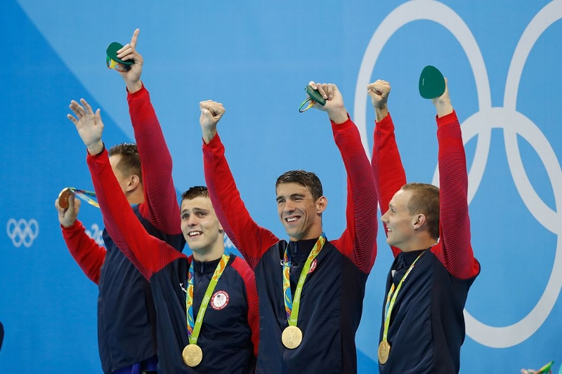 Michael Phelps and other members of the US Men's 4 x 100m freestyle swimming team after winning gold in Rio. Image Source:  Fernando Frazão/Agência Brasil via Wikimedia Commons CC