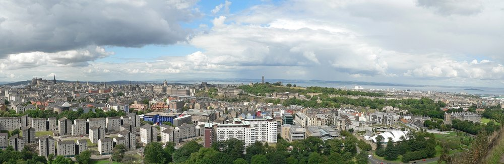 Spectacular panoramic image of Edinburgh and the Firth of Forth from Salisbury Crags. At left in the distance is Edinburgh Castle and the spire of the Hub, while the Nelson Monument stands tall atop Calton Hill just off the Center. Below it to the right are the Scottish Parliament and Holyrood Palace. Image Credit:  Oliver-Bonjoch  via  Wikimedia Commons   CC