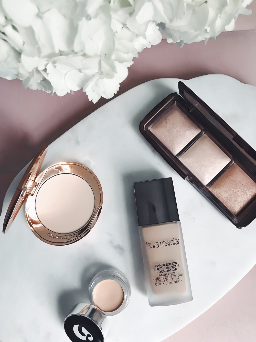 Recent Beauty Buys | Pine Barren Beauty | Laura Mercier foundation, Charlotte Tilbury setting powder, Glossier concealer, Hourglass ambient light palette, beauty product review, beauty product flat lay