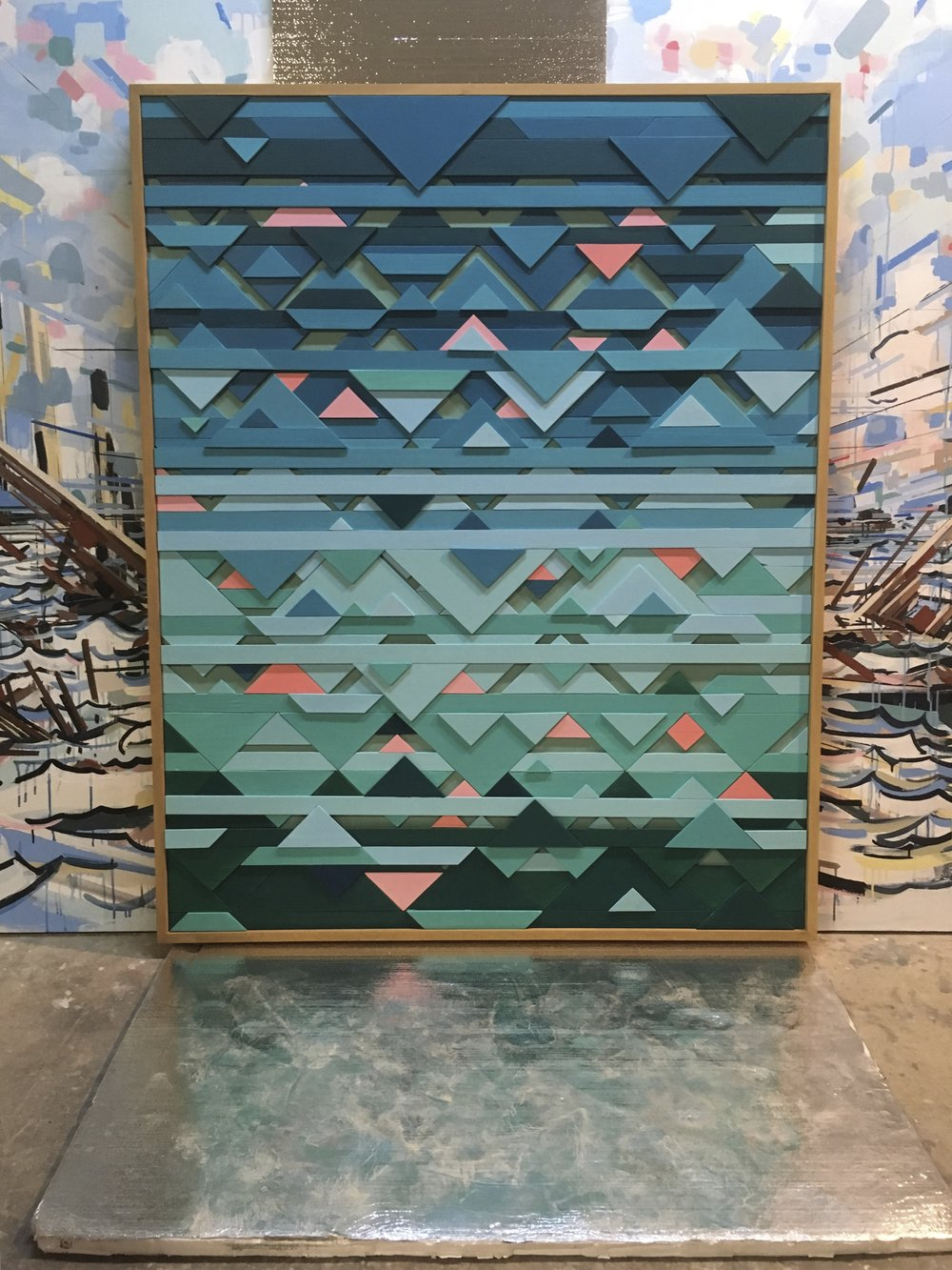"Triangulated Horizons. 48x60x3"". Wood, paint. Private Collection Austin, TX. Background: 8x24' painting in progress."