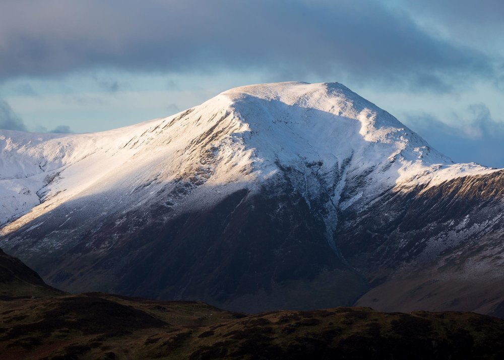 snow capped hindscarth catching golden light at sunrise taken from cat bells keswick cumbria lake district mountain.jpg