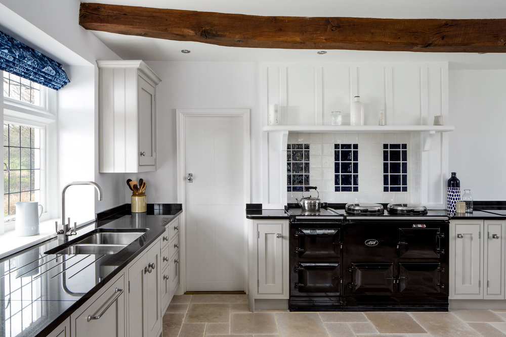 This image shows the new cabinetry, worktops and sink. These surround the Aga stove along with the original shelving and wall panelling. One of the original beams is also visible here.