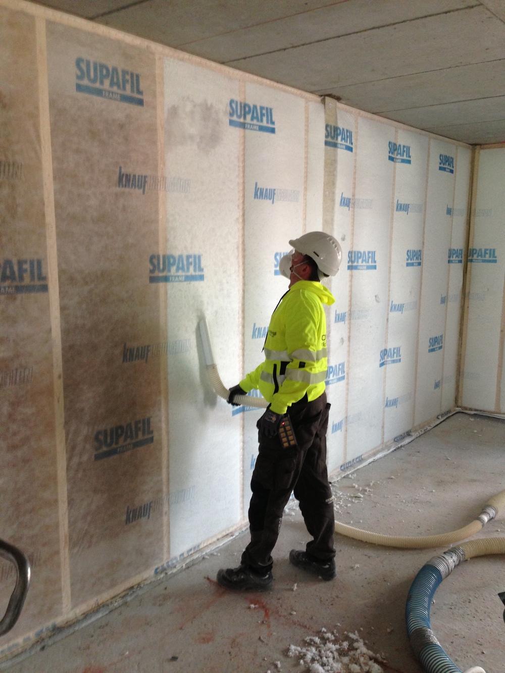 Pågående blåseisolering av vegger i nybygg