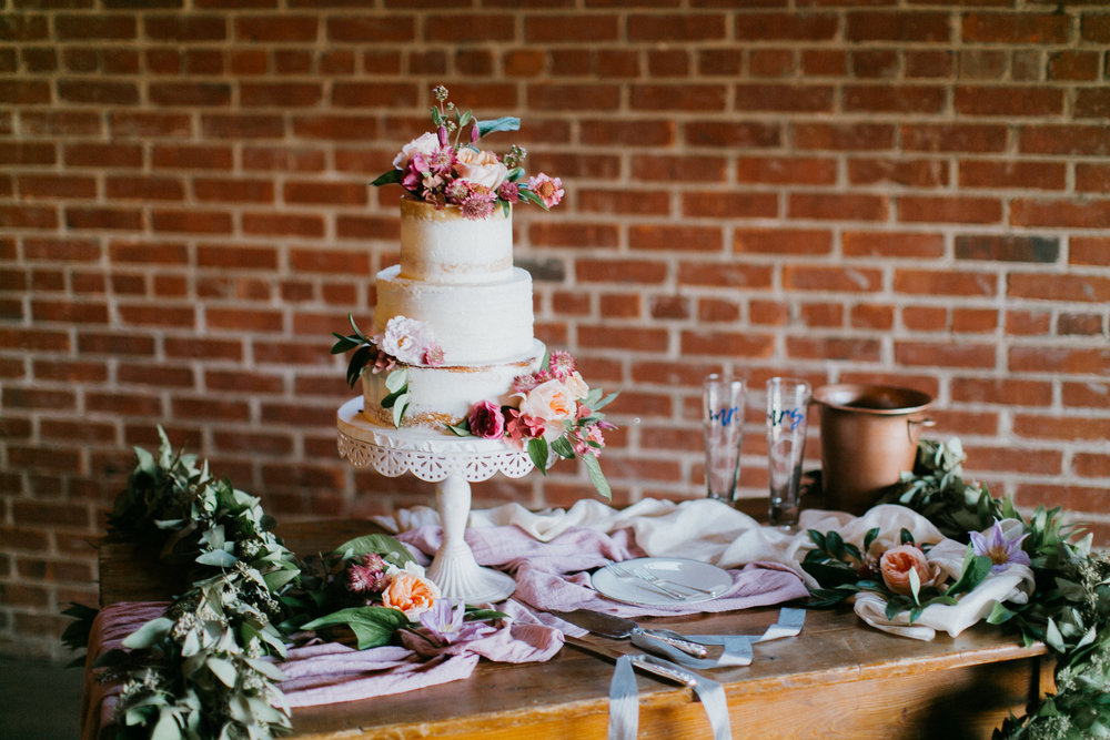 Simple Barelay naked cake decorated with flowers in rustic warehouse setting.