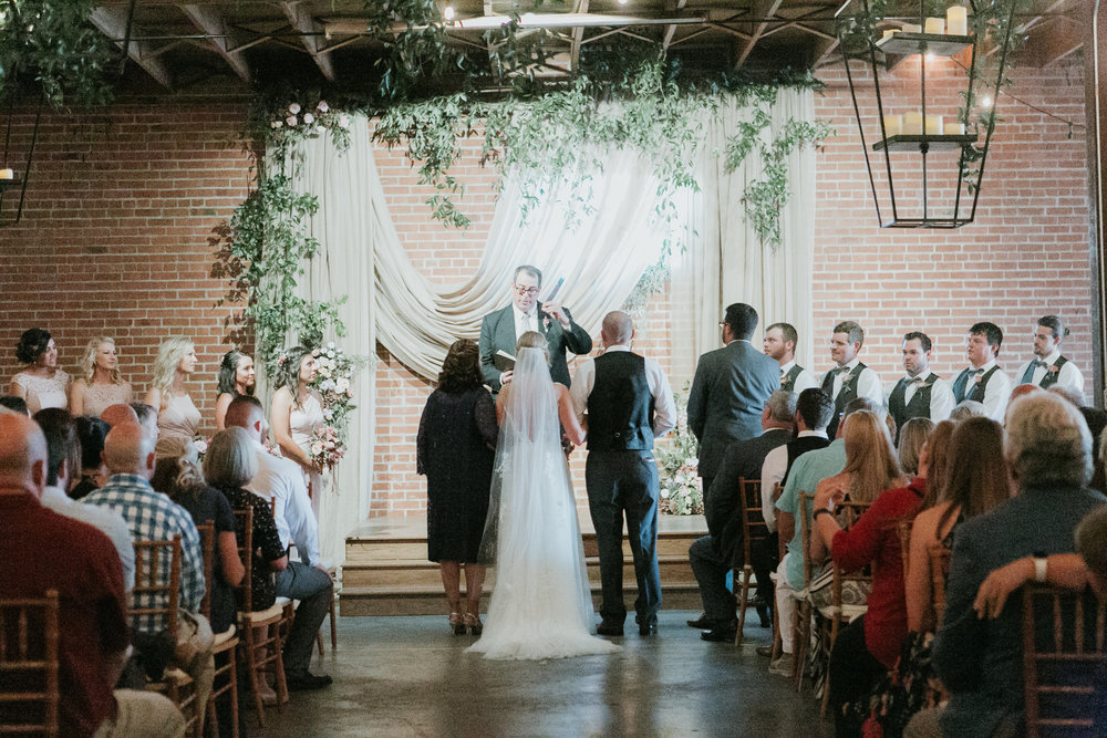 Fabric and smilax ceremony backdrop