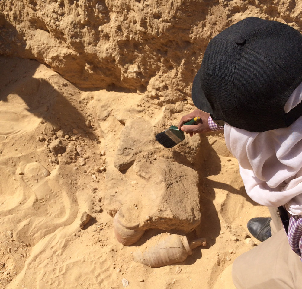 Fathy cleaning the mud brick layer above today's human skeleton.  Offering jars and ushebtis visible in the foreground.