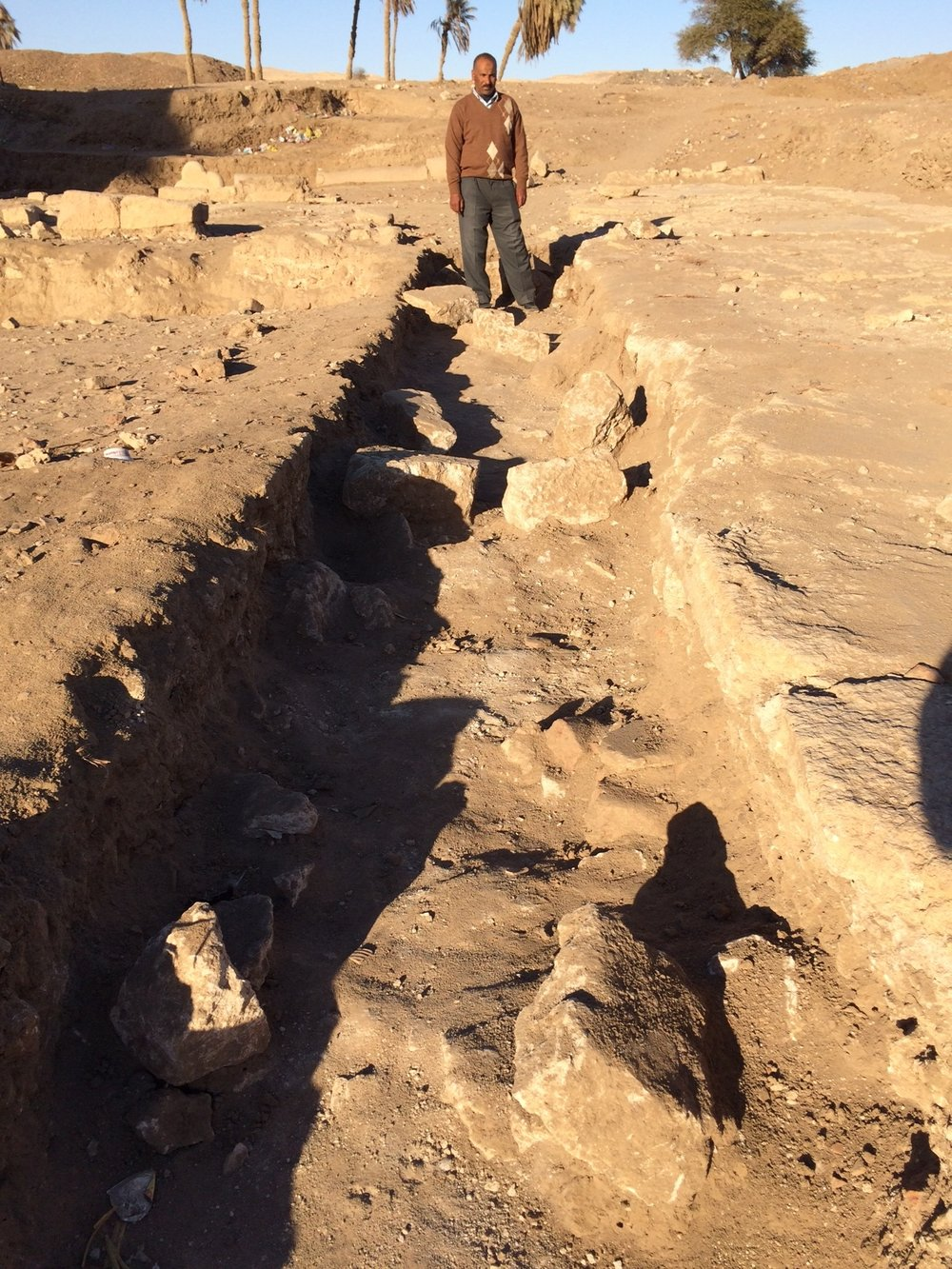 Fathy in the colonnade foundation trench showing intact mortar leveling course and some scattered foundation stones.
