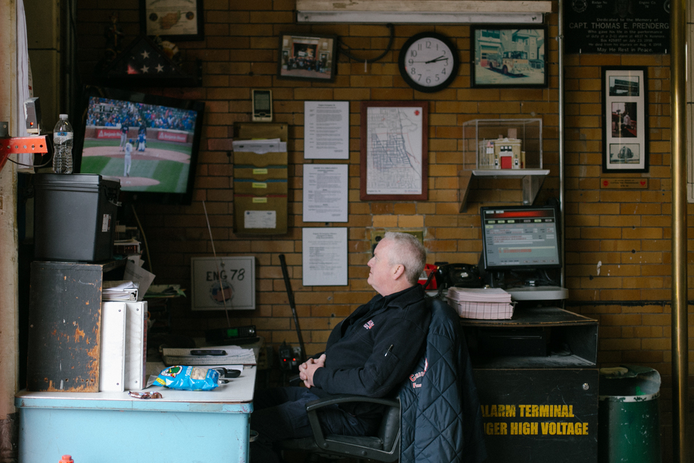 John, a 20 year veteran of the Chicago Fire Department takes a break to watch the Cubs game. The station is across the street from Wrigley Field. They can hear the action but can't see it. 5/25