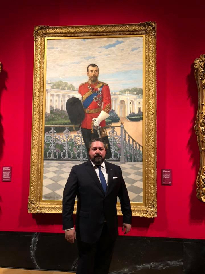 "The Grand Duke poses before Nikolai Bogdanov-Belsky's ""Nicholas II, Emperor of Russia"" Signed and dated 1908. The Grand Duke is Nicholas II's first cousin thrice removed."