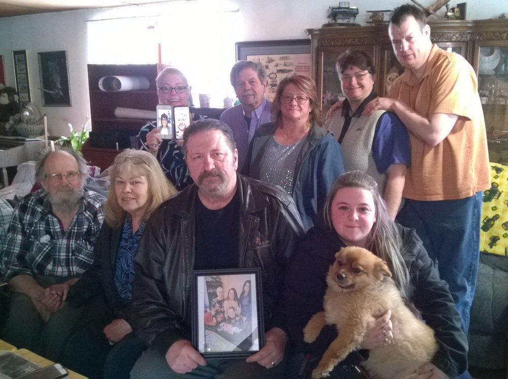 """Pegge McDonald's family at her Butte home recently. From back left: Daughter, Peggelee, holding cell phones with grandchildren, Angel Christensen and Kelly David Christensen, on Facetime; Pegge's son, Willie Christensen; Willie's wife, """"T.C.""""; Pegge's granddaughter, Fanetta Higley; Fanetta's husband, Kenney. Front row left: Pegge's husband, Roger McDonald; daughter-in-law, Ginger Christensen; Pegge's son, Kelly Michael Christensen, holding Pegge's favorite family photo; and granddaughter, Calla Christensen, with Pegge's Pomeranian."""