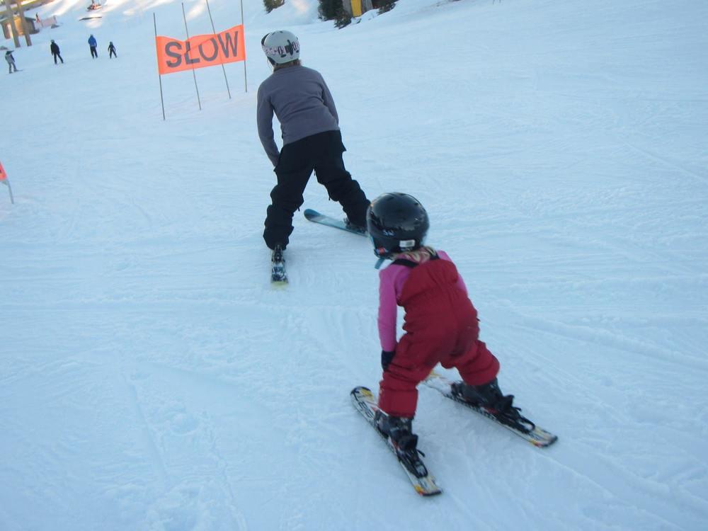 charlotte teaching a 4-year old beginner skier