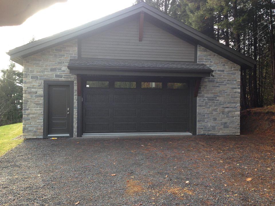 Construction d'un garage neuf. Le revêtement extérieur est en Fraser et en pierre collée. Il est muni d'une porte de 16'.