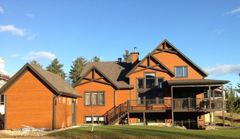 Construction neuve en 2013, vue arrière. Avec un beau rez-de-jardin et un cabanon construit en harmonie avec la maison.