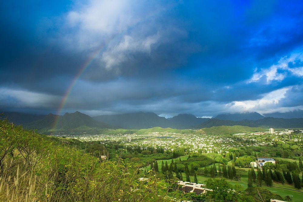 Rainbow over green valley in mountains of Oahu Hawaii