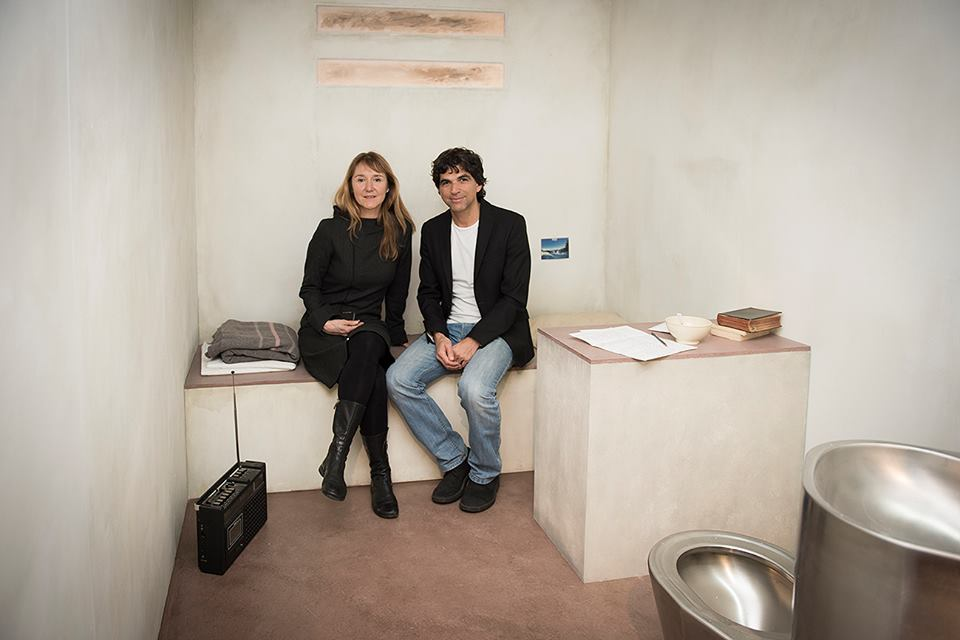 Anne-Frédérique Widmann and Patrick Chappatte seated in the   Windows on Death Row    life-size reconstruction of a prison cell.