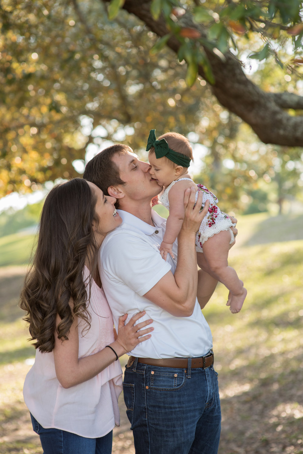 mom and dad kissing baby under tree- Pensacola Family Photographer