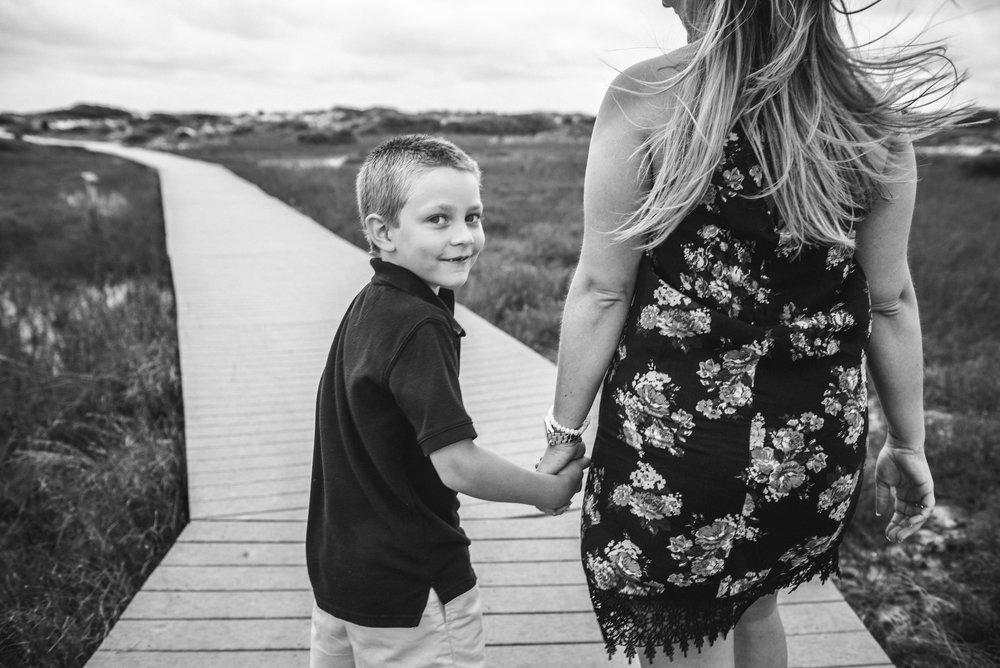 boy holding moms hands on boardwalk-Penacola Vacation Family Photographer