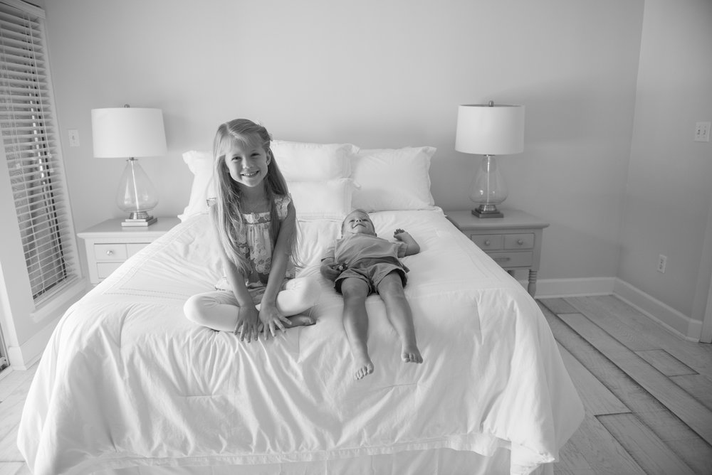 brother laying on bed with sister sitting-Gulf Breeze In-home Photographer