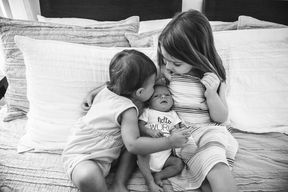 sisters kissing baby- Pensacola Lifestyle Newborn Photographer