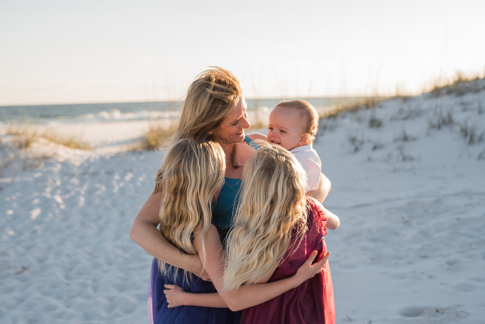 girls hugging mom and mom with baby