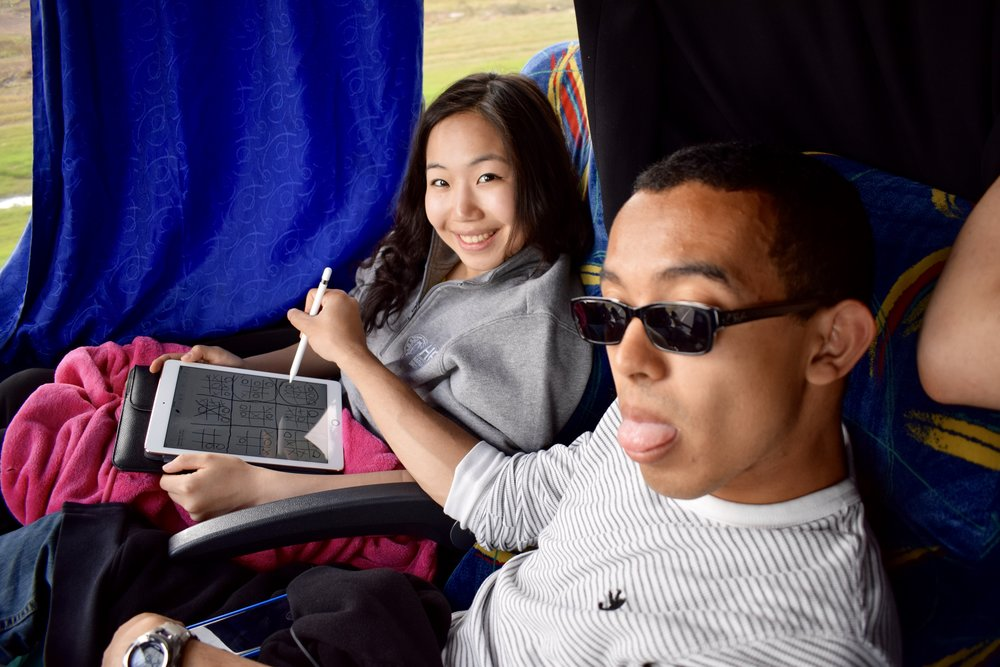 Enchi Chang '17 and John Austin '17 engage in a battle of wits to pass time on a bus  Photo by Ellis Yeo '20