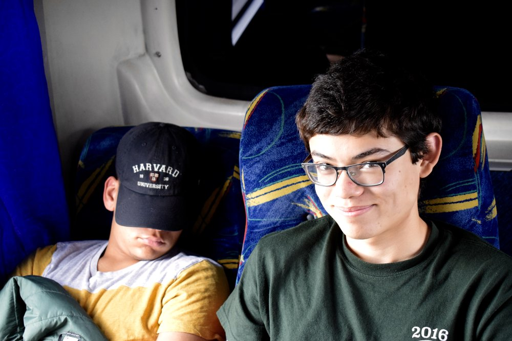 On a bus, Alejandro Gracia-Zhang '20 smiles as Myer Johnson-Potter '20 takes a snooze  Photo by Ellis Yeo '20