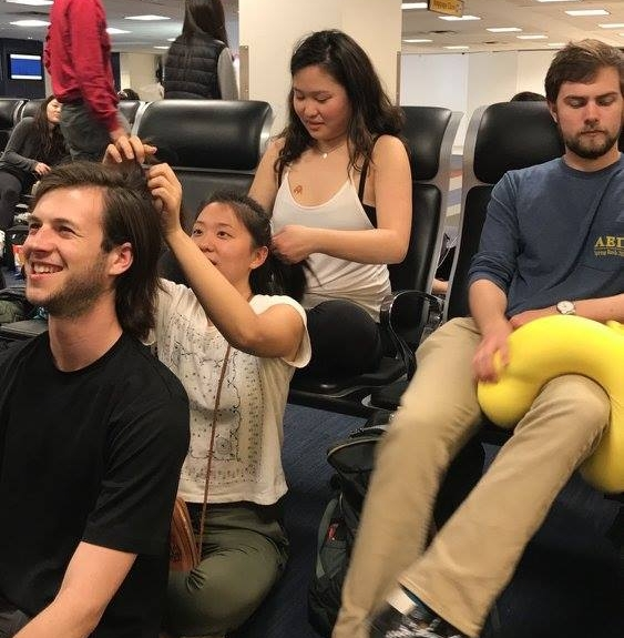 Luke Fieweger '16, Anes Sung '16, and Dominique Kim '17 form a hair-braiding train as Patrick Sanguineti '17 adjusts a travel pillow on his leg  Photo by Ellis Yeo '20