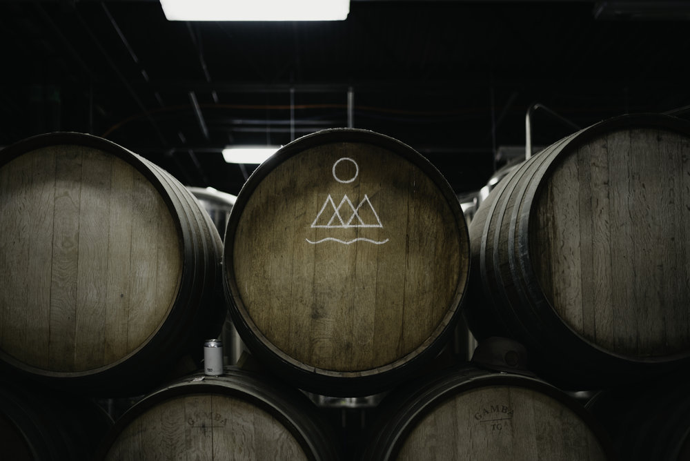 Photo of our barrels behind our bar with our logo