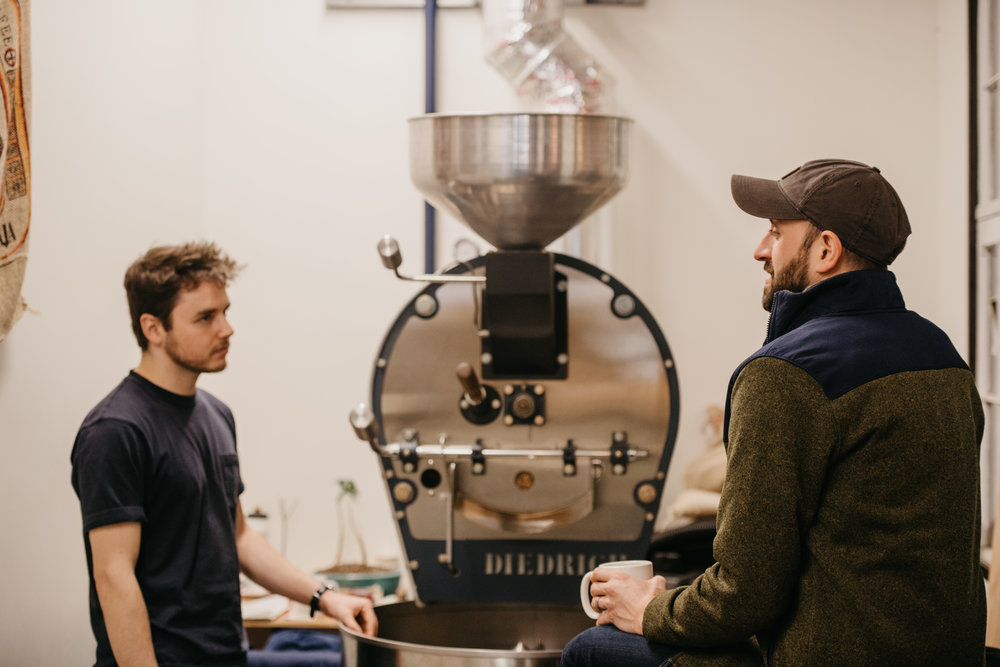 Photo of Jesse and Alex discussing the coffee roasting process