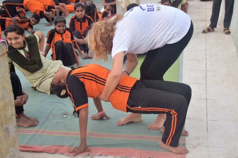 Tatiana helping a girl with bridge pose.jpg