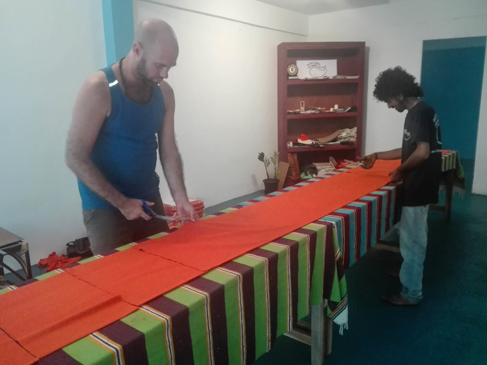 Blake and Krishna, our local Coordinators in India, cutting cloth for the bags in our Marine Conservation Centre in Kovalam.