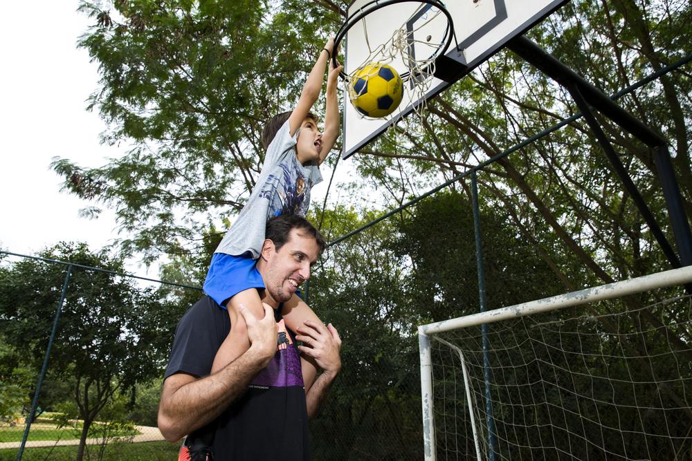 Nos ombros do pai, Gustavo faz uma cesta