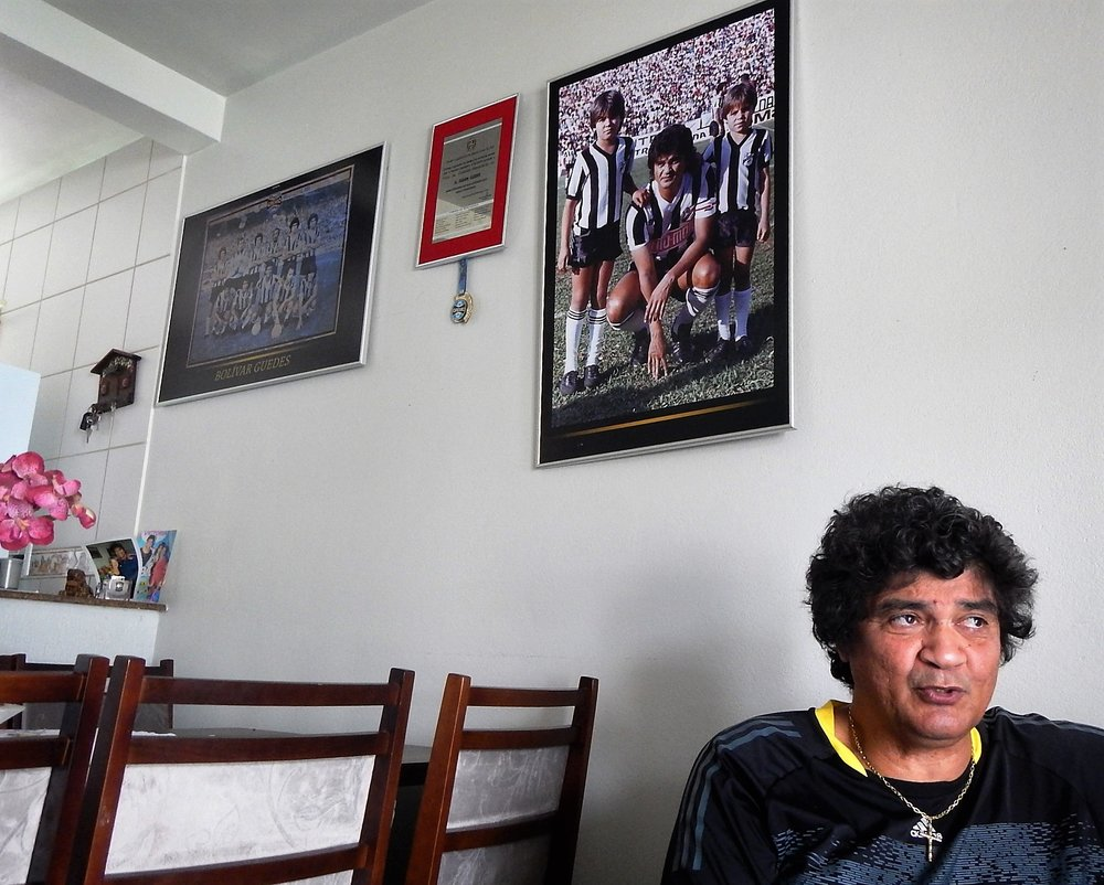 Bolívar sentado na sala de casa, debaixo da foto com os filhos ainda crianças. Um deles, Fabian, foi campeão 12 vezes pelo Inter, sendo duas da Libertadores. O outro se chama Marcel