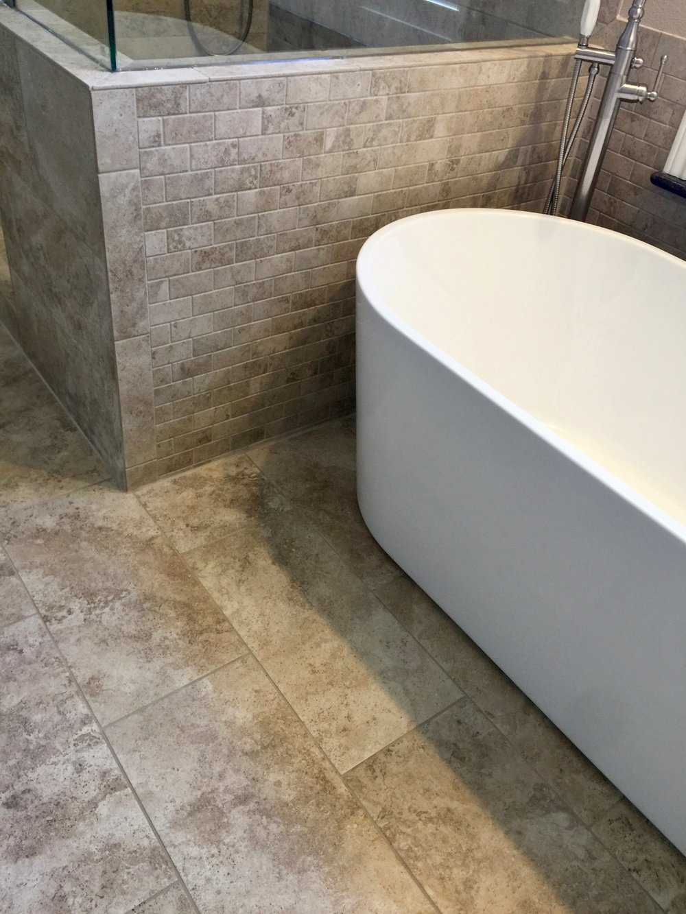 12x24 tile floors in matching tile with classic white stand alone tub.