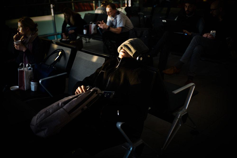 J'ai de la chance, je prends souvent l'avion.  Je n'arrive pas à m'en lasser.  +6 heures de décalage horaire, -5 heures de décalage horaire.  Dans les aéroports, une constante, c'est cette foule fatiguée qui cherche quelques minutes d'un repos inconfortable en attendant de voir s'afficher sur l'écran « embarquement porte 26 ».  Mes voisins de voyage ont comme partenaire de sommeil en plus d'un fauteuil rigide, un soleil trop matinal ou trop nocturne.  Voici les dormeurs du terminal 2