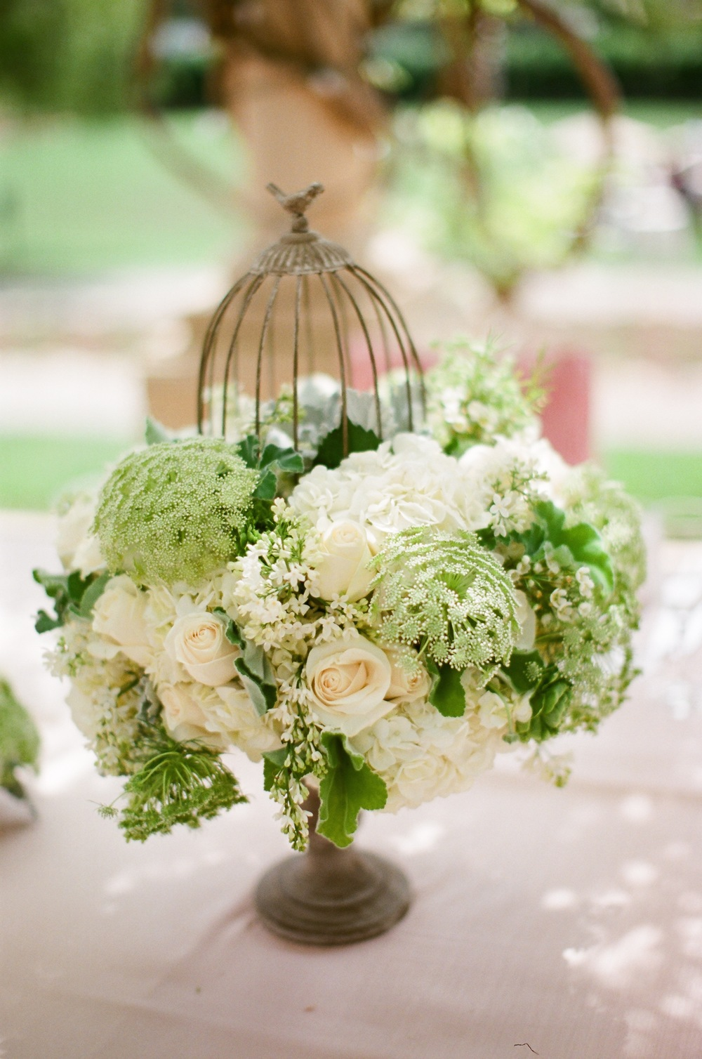 "If you like an eclectic feel consider using unique and interesting vessels for your floral centerpieces.  This was a birdcage on a pedestal that added a lot of interest to the table and gave my bride that garden""y"" feeling she was looking for.  Photos:  Anna Costa   Florals:  Butterfly Floral Events   Venue:   Ojai Valley Inn & Spa"