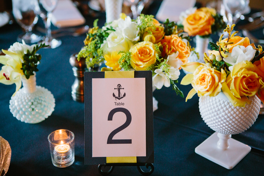"This groom was in the navy and he called his bride his ""yellow rose of Texas"" so the centerpieces on the tables reflected these two things perfectly.  The yellow florals in white milk glass containers popped clean and bright on a dark navy linen.     Photo by: Lavender & Twine Venue: Ojai Valley Inn & Spa Florals: Your Image Florals"