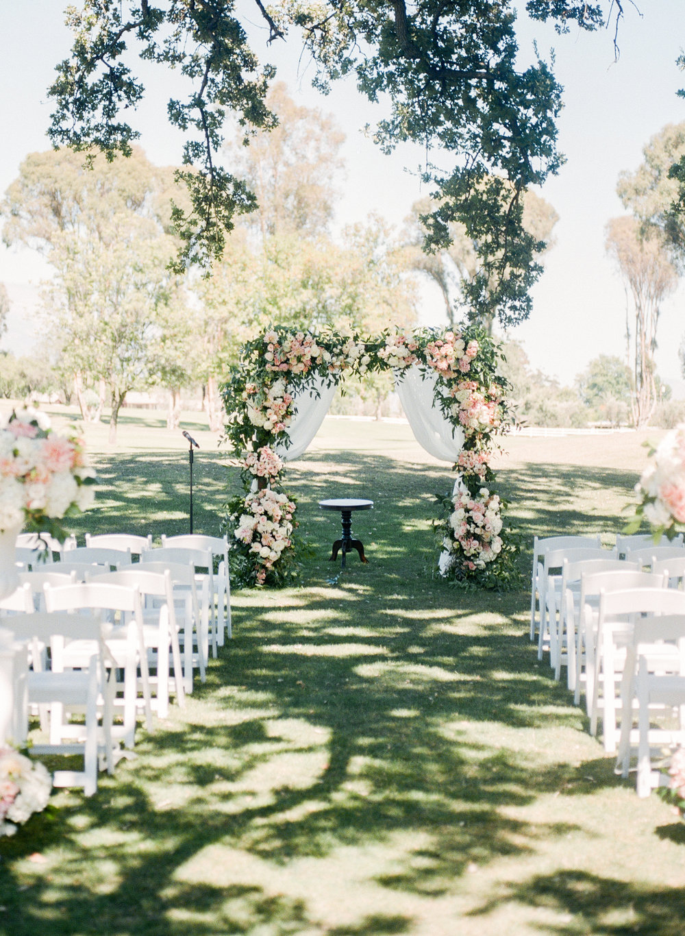 Ojai Valley Inn ceremony site with blush and ivory floral arch