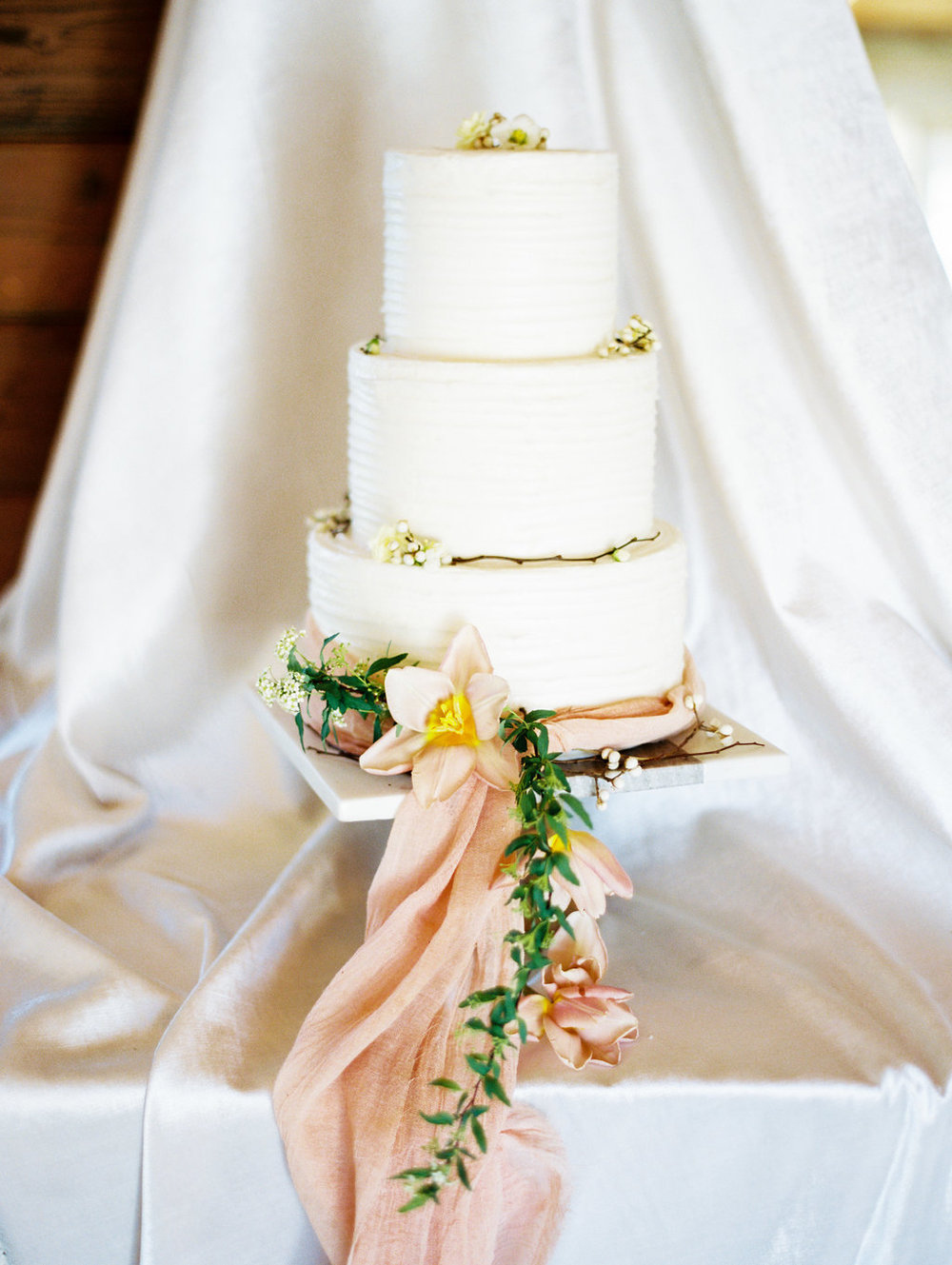 four-tiered wedding cake with floral and ribbon accents