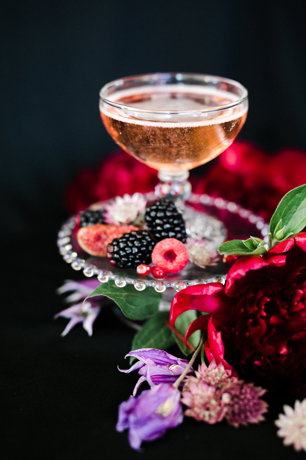 champagne and berries on vintage glass dish