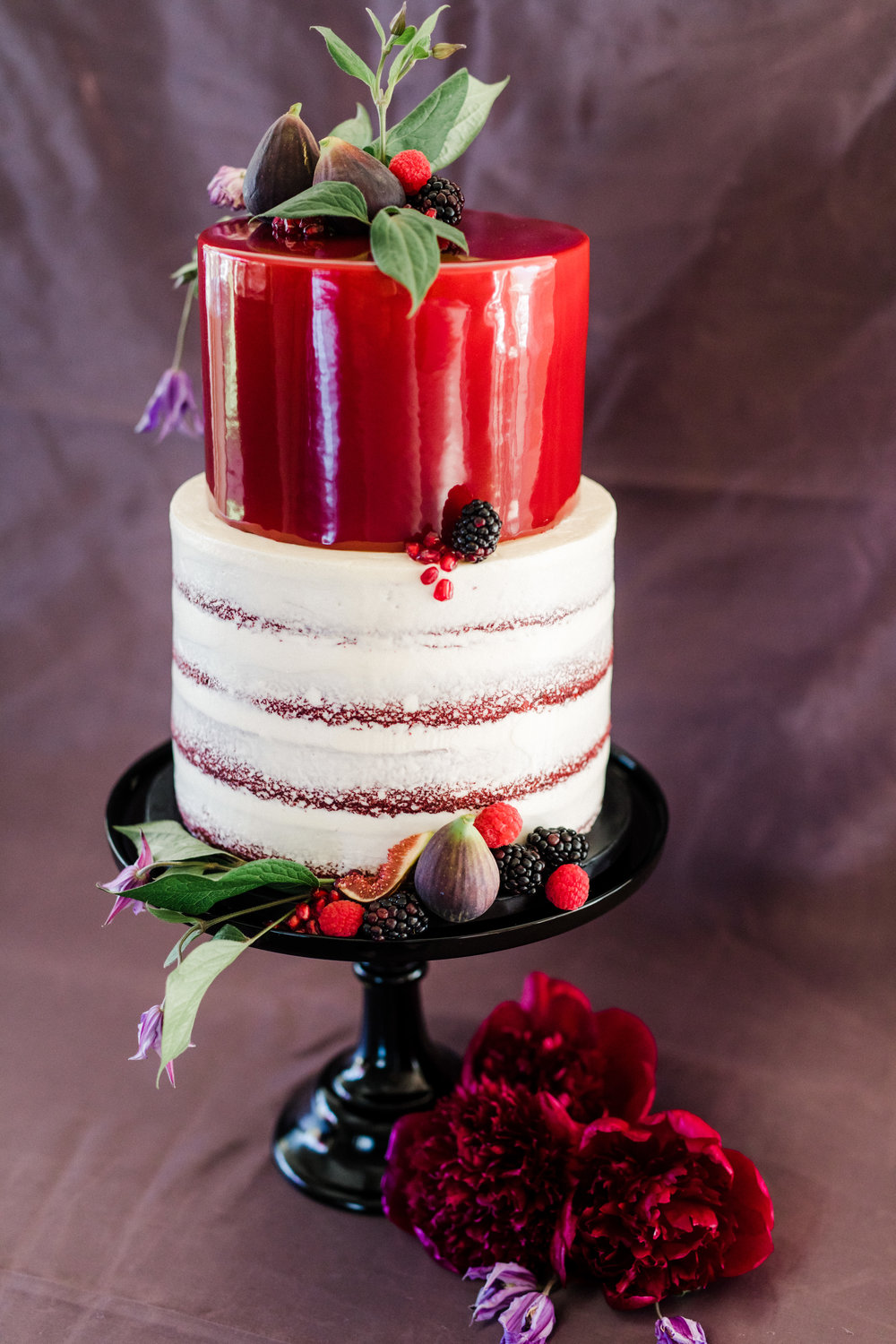 burgundy and white wedding cake with floral and fresh fruit accents