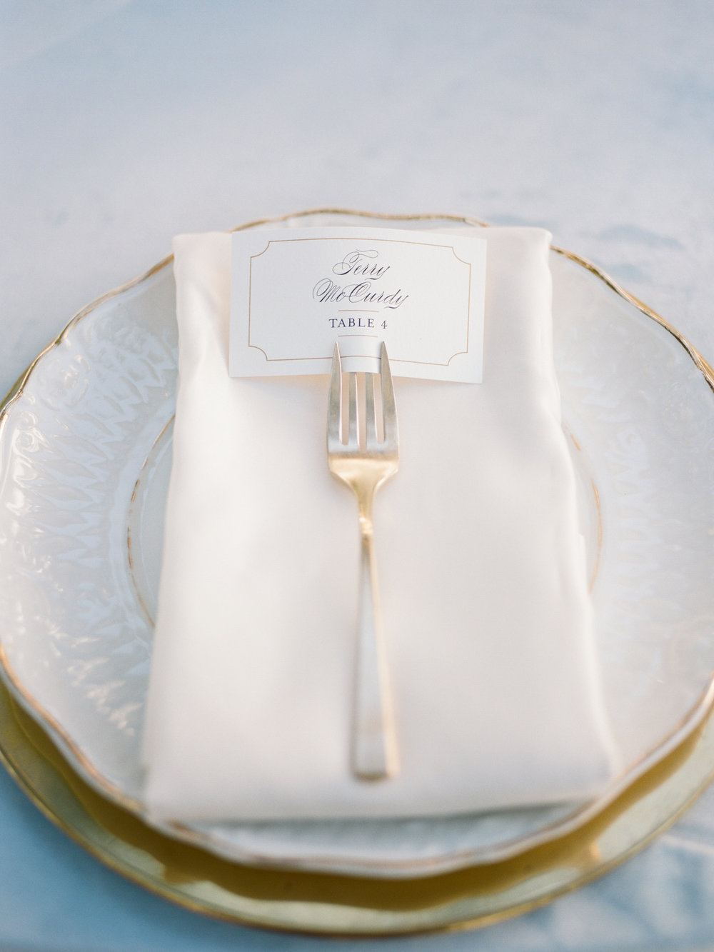 ivory and gold place setting with vintage silver flatware